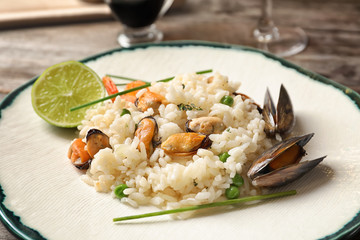 Plate with delicious seafood risotto on table, closeup