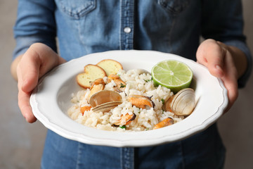 Young woman holding plate with delicious seafood risotto on blurred background