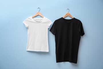 White and black t-shirts on color background. Mock up for design