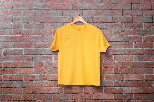 Yellow t-shirt on brick wall background. Mock up for design