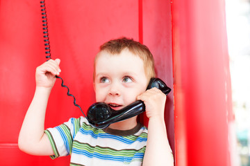cute boy talking on the phone in a red telephone box. little kid holding a telephone receiver and smiling
