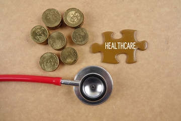 Medical concept with stethoscope,piece of puzzle and coins .