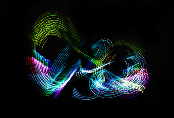 Light painting (light motion) with colored neon lights of various rainbow colors isolated on black background