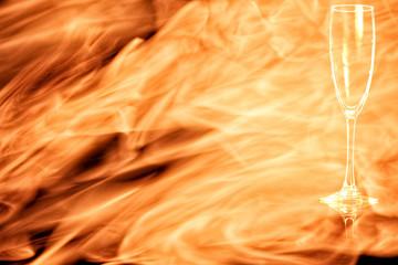 En empty champagne flute in the fire flames.