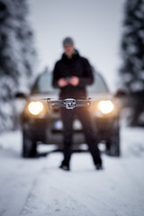 Young man flying a drone in winter forest. Image with lastest drone technology.