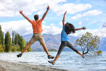 Wall Mural - New Zealand tourists couple jumping of happiness at Wanaka Lone . Happy young people doing funny jump of joy sightseeing traveling in summer adventure destination. Woman and man.