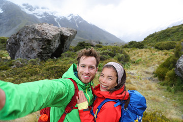 New Zealand travel selfie happy couple backpackers hiking. Travel selfie couple hikers taking smartphone picture on outdoor trail hike in outdoor nature. Active healthy happy people.