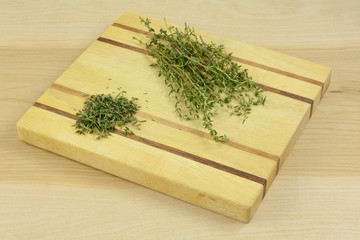 Fresh thyme leaves being separated from sprigs of thyme on wooden cutting board