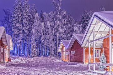 Garden Poster Scandinavia Travel Destinations Concepts. Traditional Reddish Lapland Suomi Houses Over the Polar Circle in Finland at Christmas Time. Located in Front of Amazing Winter Forest Scenery in Finland