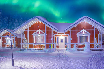 Spoed Fotobehang Scandinavië Travel Destinations Concepts. Beautiful Multicoloured Vibrant Aurora Borealis known as Northern Lights Playing with Vivid Colors Over Traditional Lapland Houses in Finland.