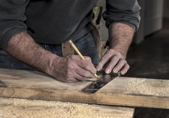 Closeup of carpenter's rough hands using a pencil and old square marking a line on a wood board to cut with sawdust around