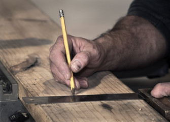 Closeup of carpenter's rough hands using a pencil and old square to mark a line on a wood board to cut using a chop saw