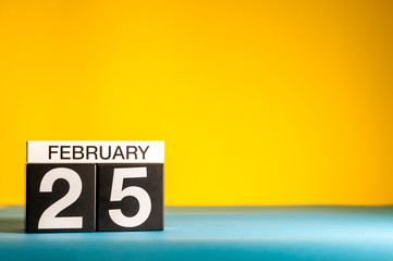 February 25th. Day 25 of february month, calendar on yellow background. Winter time. Empty space for text