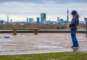 Boy operating his drone in the morning at Primrose hill, London