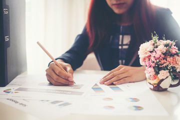 Business woman holding a pencil is working with business chart grpah checking infomation inside.