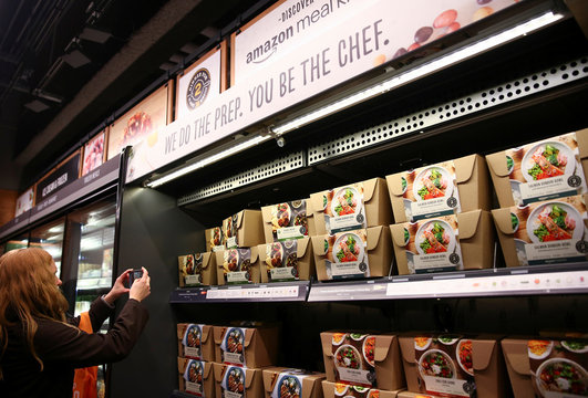 A visitor takes a photo of the Amazon meal kits section in the new Amazon Go store at Amazon's Seattle headquarters in Seattle