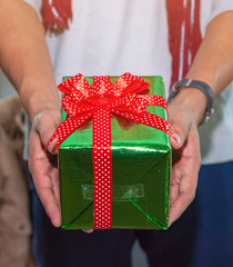 Close up of man hands holding a gift box wrapped with red ribbon. Small gift box in . hands of a man at home. Shallow depth of field with focus on the little box.