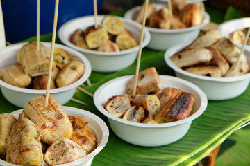 Grilled sliced banana in foam bowls with wood stick on green banana leaf