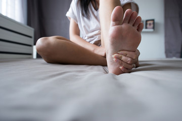 Woman massaging her feet on bed