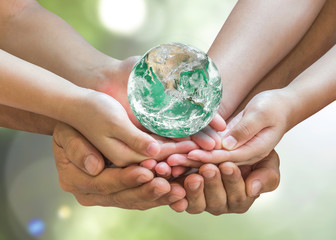 Green globe in family volunteer hands (father parent - children) for environmental protection, earth day, kindness charity donation, CSR with people concept. Elements of this image furnished by NASA