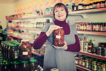 Glad buyer choosing canned jar of tomatoes