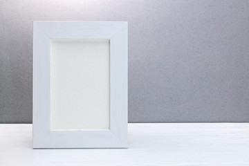 empty wooden white photo frame against grey background