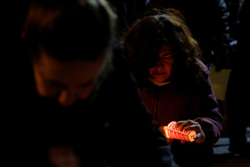An earthquake victim lights a candle next to others as they take part in a farewell ceremony to their homes in a building in Pacifico 455, damaged during the September 2017 earthquake in Mexico City
