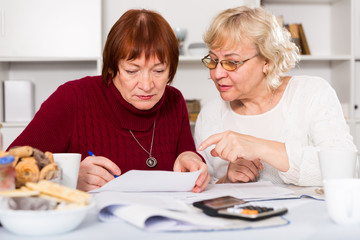 Worried mature female friends with papers