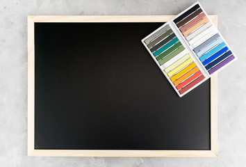 Back chalkboard mockup with colorful chalks on grey background. Business, interior design, lettering concept. Text space