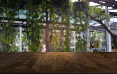 image of wooden table in front of abstract blurred background of outdoor garden lights. can be used for display or montage your products.Mock up for display of product.