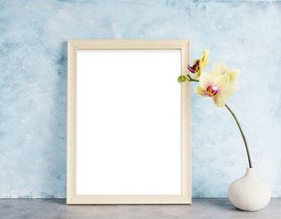 Bright photoframe mockup with yellow orchid against  light blue wall. Interior design concept. Text space