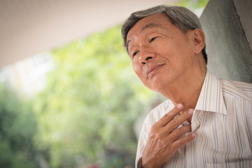 sick old man with sore throat or cold or flu, unhealthy old man portrait