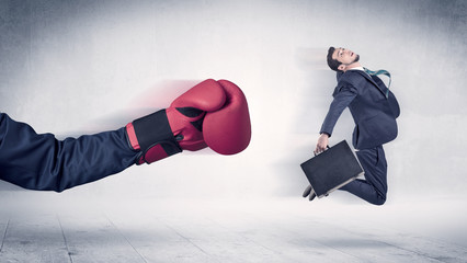 Huge Boxing Gloves punches businessman concept