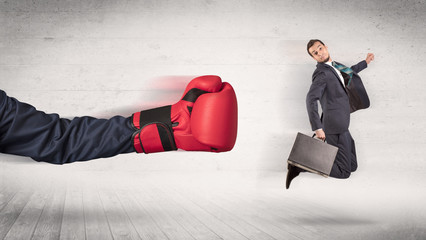 Arm with boxing gloves hits office worker concept