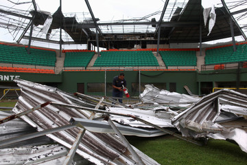 """A man finds a fire extinguisher between the rubble of the baseball stadium Felix """"Nacho"""" Millan, in Yabucoa"""