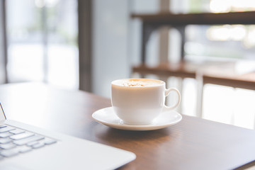 Coffee cup and laptop for business in coffee shop in the morning