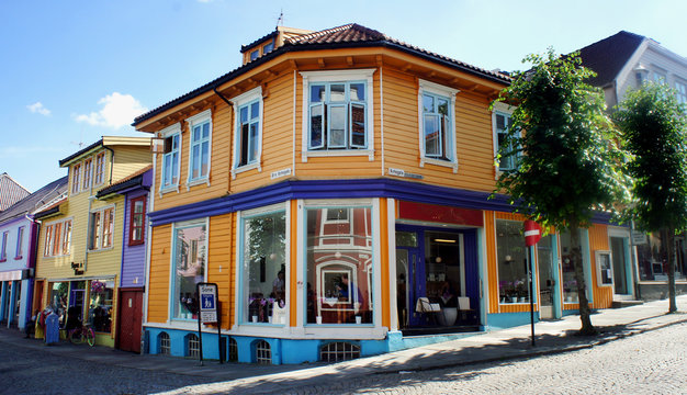 Stavanger, Norway - Famous old colorful wooden cottages in city center, traditional multi colored facades with cafe in the street