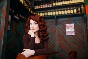 Beautiful girl with makeup, wavy and red hair, red burgundy lips, looks frame, in background cafe