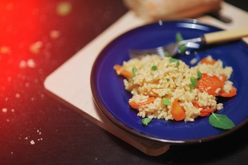 Pilaf of rice with apricots, mint leaves, in a dark blue plate on a wooden Board on black background.
