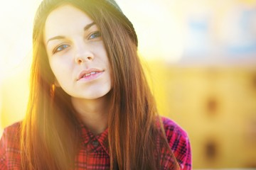 Closeup portrait of relaxed caucasian woman with long hair in a red checkered shirt, looking at camera outside in Park the sun. Beauty, fashion, lifestyle concept