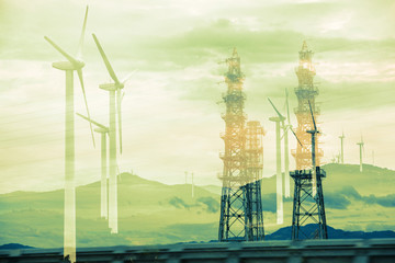 Renewable energy concept. Double exposure of Wind mill and transmission towers.