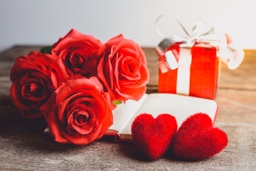 Red roses, red heart, notebook and gift box on a wooden background