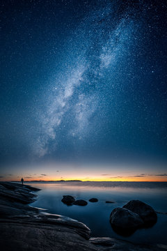 Beautiful view of milky way glowing on the sky with calm sea and a man looking at the stars and sunset
