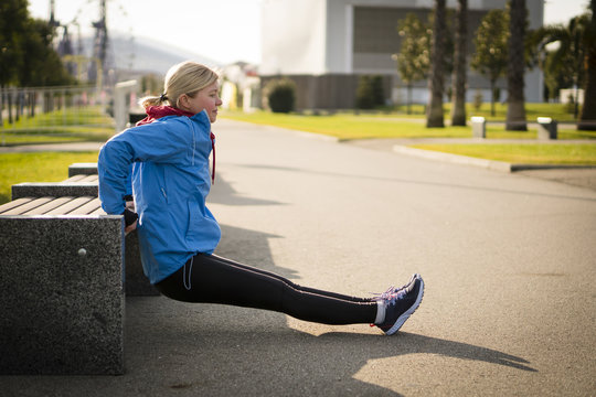 Sport, exercising, training and people concept - woman doing triceps dip exercise on city street bench.