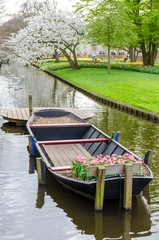 Boat with tulips on water canal in Keukenhof garden park from Netherlands (Holland).