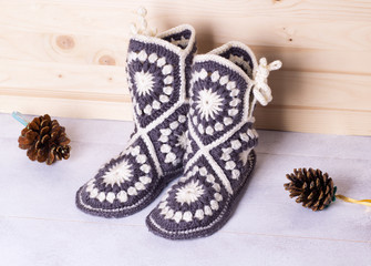 crochet boots for adults on wooden background