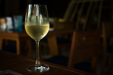 Glass with cold white wine at restaurant