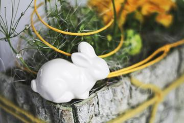 Desorative easter bunny made of ceramic sitting on flower arrangement