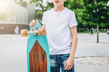 Summer day. Young millennial boy dressed in white t-shirt is stands outdoor. Mock up. Space for logo, text, image.
