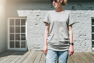 Summer day. Front view. Young millennial woman dressed in gray t-shirt is stands against gray brick wall. Mock up. Space for logo, text, image.